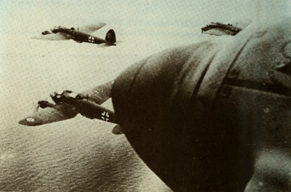 A flight of Heinkel HE 111 medium bombers approach the coast of England flying low over the channel. Such formations became a familiar site to Londoners, the HE 111 being the major type in these raids. Originally conceived as a civil airliner for Lufthansa, it was employed by the Luftwaffe in a large number of variants as one of the most flexible German designs of the war. The HE 111 was also exported for operation by the air forces of China, Hungary, Romania, Spain and Turkey.